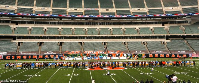 The Los Angeles Chargers and the Cincinnati Bengals stand on the field during the national anthem at the beginning of their game at Paul Brown Stadium on Sunday