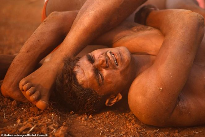 A fighter winces in pain as he is pinned to the ground.Kushti wrestling schools train wrestlers with a strict 12 hours-a-day training regimen