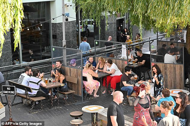 Ahead of the new restrictions, Brits hit pubs, parks and beaches at the weekend for one last knees-up with friends and family. Pictured, People enjoy a drink outside a pub in Camden yesterday