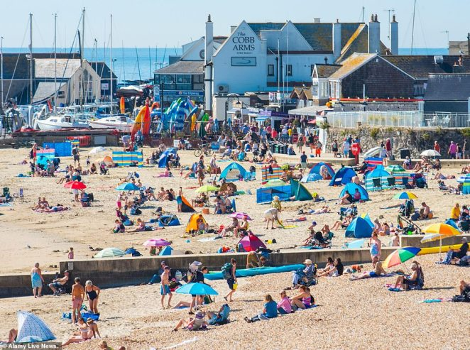 Beachgoers and September staycationers soak up the sun on the beach at the seaside resort of Lyme Regis in Dorset