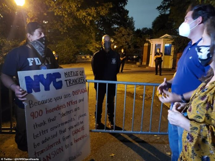 """A sign read: 'Because you are displacing 900 homeless NYers and think that """"shelters are better environments"""" please be advised that you will be transferred from Gracie Mansion to a homeless shelter'"""