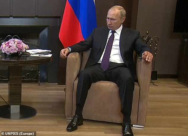 At ease: Putin made himself comfortable during the summit at the Black Sea resort of Sochi
