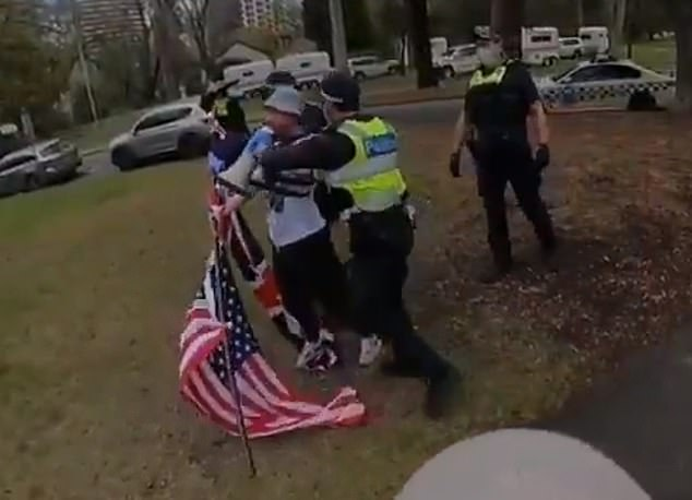 The police were not impressed. Three officers tackled the protester, taking his megaphone and grabbing his flag pole. Pictured: the first officer moves in