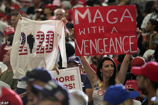 Supporters wave a 'MAGA with a Vengeance' sign