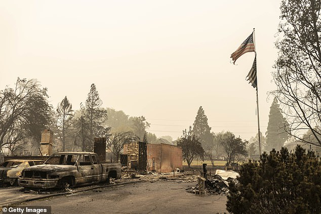 Tens of thousands of people have fled their homes as the fast-moving flames turned neighborhoods to nothing but charred rubble and burned-out cars. A US flag flies at a burnt home in a neighborhood destroyed by wildfire on Sunday