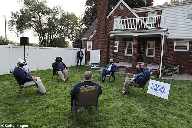 Wearing a face mask to reduce the risk posed by the coronavirus, Democratic presidential nominee Joe Biden talks with members of the United Steelworkers union in a supporter's back yard September 09 in Detroit, Michigan