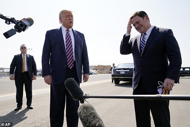 Arizona Gov. Doug Ducey removed his face mask to speak to the media under the wing of Air Force One as he stood next to President Trump