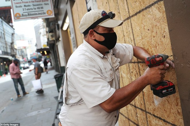Luis A. Sanabria puts plywood over the windows of a business in the historic French Quarter before the possible arrival of Hurricane Sally on Monday in New Orleans