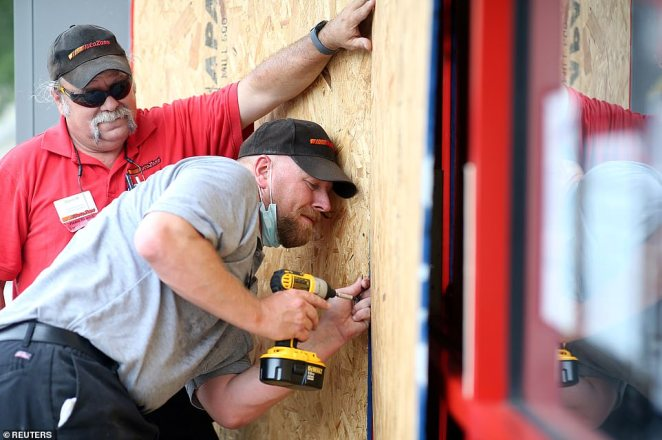 Alex Vidmar, center, and Darrin Manning board up a business as Hurricane Sally approaches in Ocean Springs, Mississippi