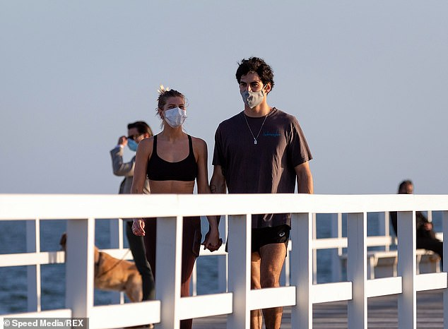 Locals wearing facemasks walk along the South Melbourne Beach on Monday. Lockdown restrictions in regional Victoria will be lifted from tomorrow