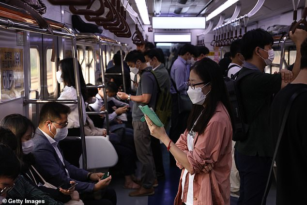 A woman wearing a mask looks at her phone on board a subway train in Seoul this morning