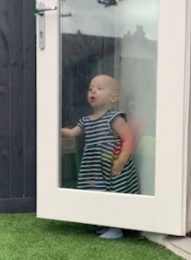 The adorable toddler does not realise that she can be easily spotted through the transparent door andstands patiently waiting to be found