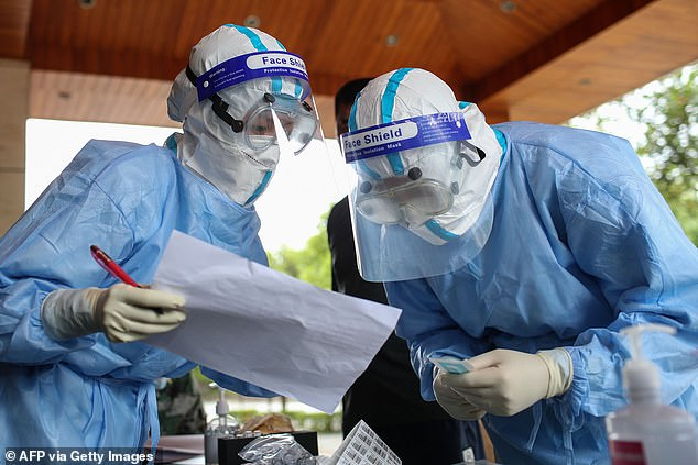 Medical workers check information as they prepare COVID-19 coronavirus testing for residents in Ruili in China's southwestern Yunnan province on September 15
