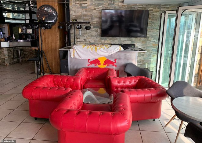 Pictured: Four red sofas sit next to the large bay windows. Behind them, a large TV screen is mounted the wall next to a portable bar surface and some disco lights