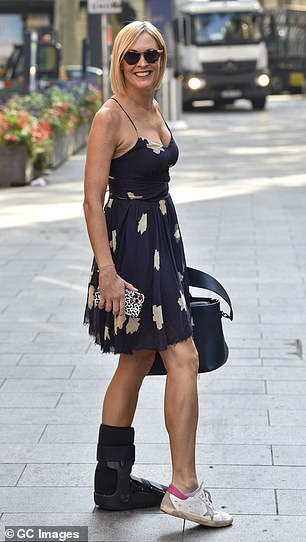 Commanding attention: The Scottish host, 44, looked typically stylish in a navy skater dress, which she teamed with her fracture walker boot