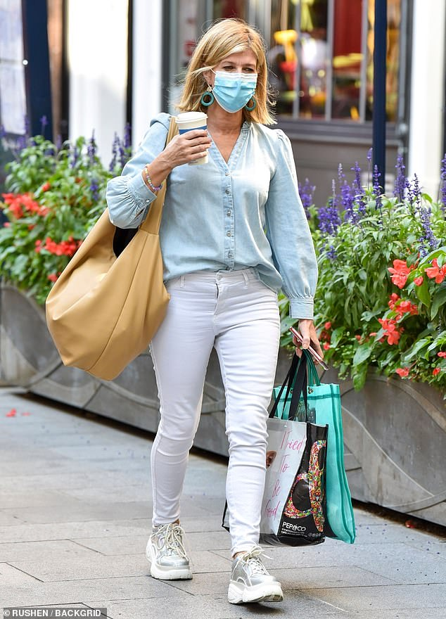Chic: Kate Garraway, 53, cut a casual figure in a blue denim balloon-sleeve blouse teamed with white skinny jeans as she left Global Studios in central London on Tuesday
