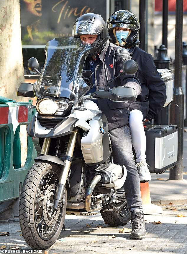 On-the-go: The TV star later donned a black waterproof coat and helmet as she climbed on the back of a motorbike following her show