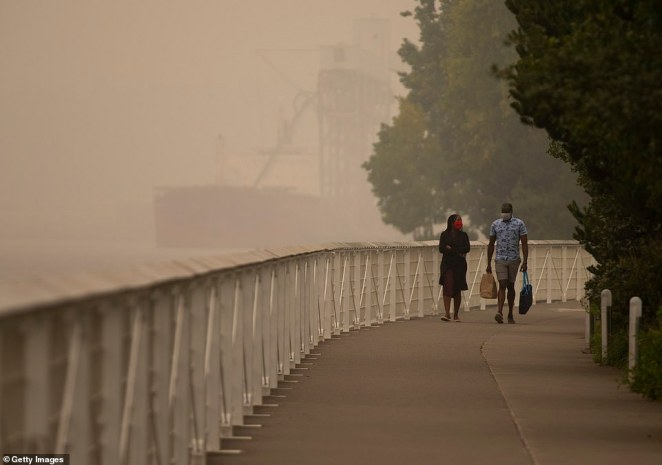 People walk near the waterfront as smoke from wildfires fills the air on September 12