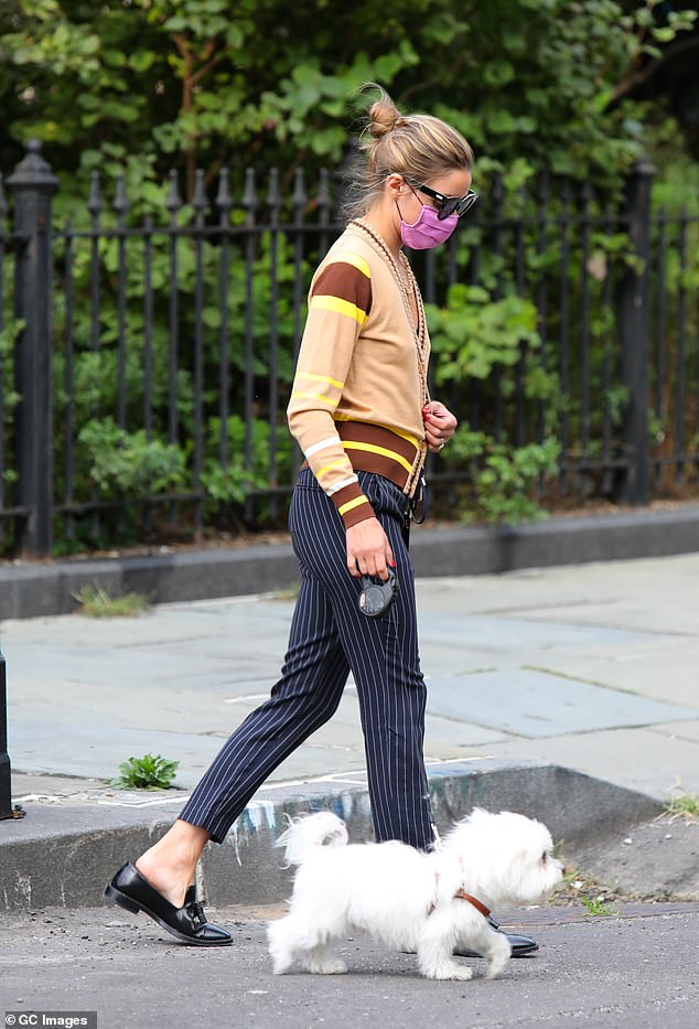Out and about: The 34-year-old fashionista also made sure to sport a face covering on her quick jaunt around the block with her pet pooch