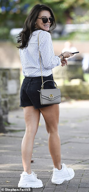 Cute:Faye paired her shorts with a pinstripe white shirt which she tied in a knot to cinch in her waist