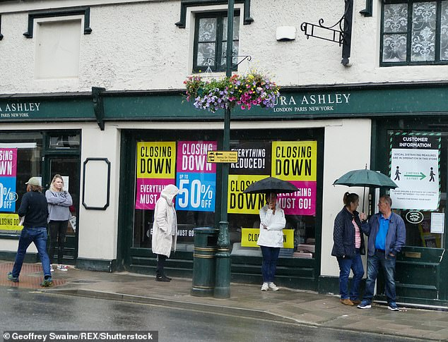 People queue in the rain at the Laura Ashley closing down sale in Henley-on-Thames, Oxford