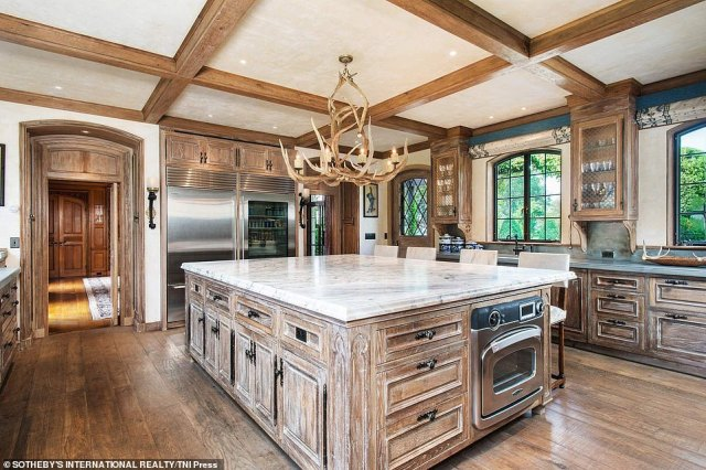This kitchen fit for any chef is decorated with antler chandeliers (top center) inside the Greenwich home