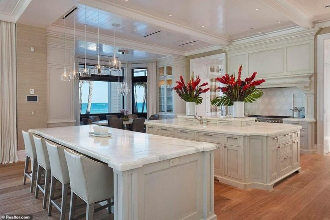 The home's main kitchen is complete with marble countertops and a large gas burner stove