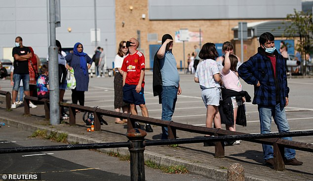 People queue for a coronavirus test outside a community centre following the outbreak of the coronavirus disease in Bury, September 15, 2020