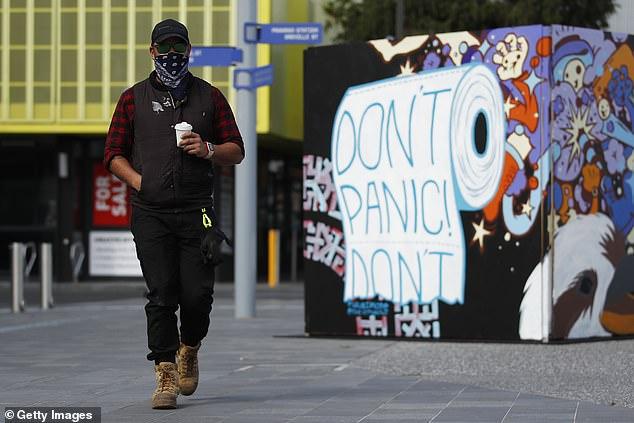A man wearing a mask walks past street art in Prahran in Melbourne on September 14