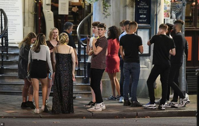 A group of revellers huddle in a group without masks as they gather on the streets in Portsmouth amid the coronavirus pandemic