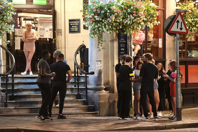Some people stand outside a pub as they swap a night in a home for a night out with their friends in Portsmouth on Tuesday