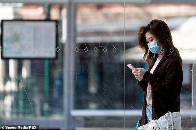 A woman wearing a mask as she waits for a tram during COVID-19 lockdowns in Melbourne in September