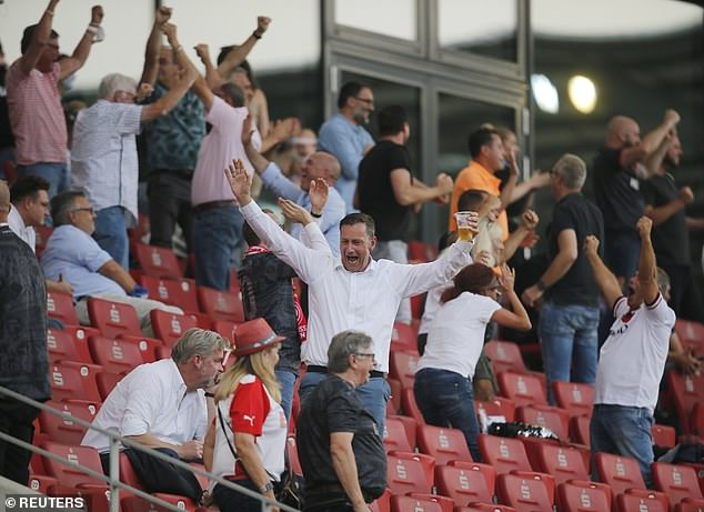 Socially distanced fans celebrate during the German Cup game between Essen and Bielefeld