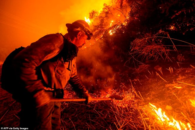A firefighter works at the scene of the Bobcat Fire burning on hillsides near Monrovia Canyon Park in Monrovia, California on Tuesday