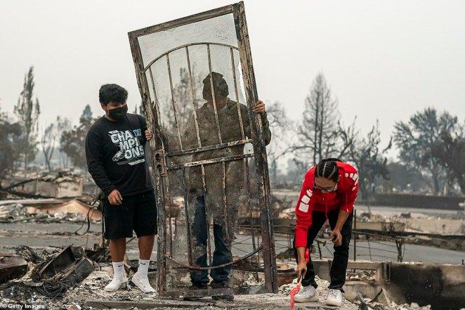 The heartbreaking return: Michael Garcia, Arath Ramirez and Leonard Barila prop up the front door to Ramirez's burned down home on Tuesday in Talent, Oregon