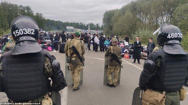 Jewish pilgrims on the road as well as lorries backed up behind them at the border crossing between Ukraine and Belarus today