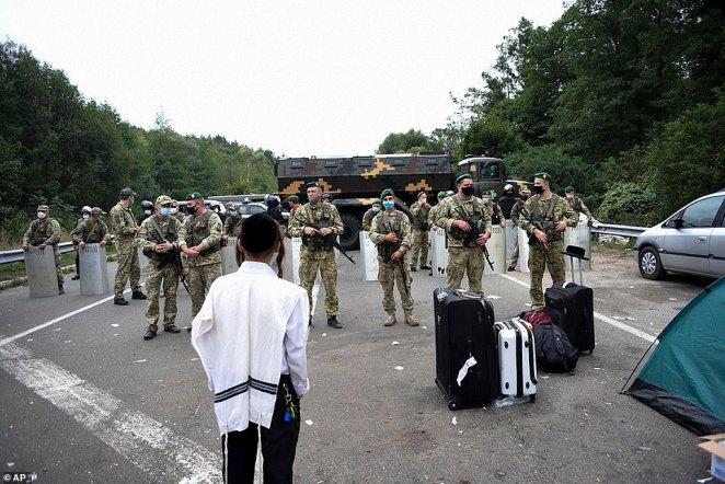 Ukrainian border guards block the road on the Belarus-Ukraine border, in Belarus, Tuesday