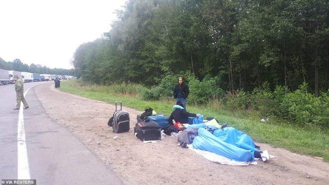 Jewish pilgrims, who plan to enter Ukraine from the territory of Belarus, rest on the roadside near Novi Yarylovychi crossing point in Chernihiv Region, Ukraine September 15