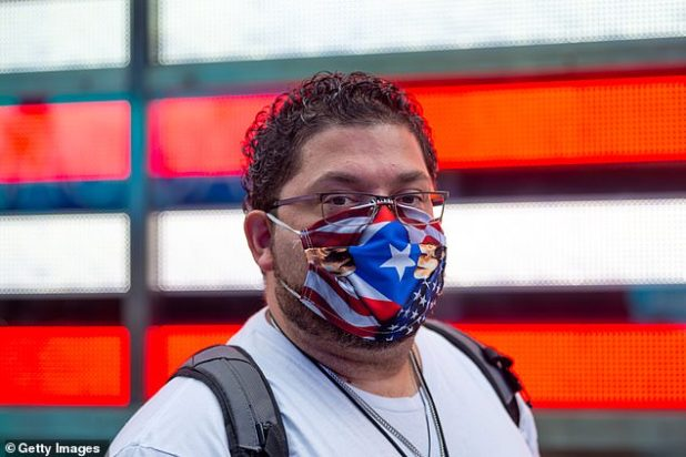 A new study found that 5.8% of the approximately 300 coronavirus patients wore glasses eight hours a day for myopia, compared to 31.5% of people in the province of Hubei.  Picture: A man wears an American and Puerto Rico flag mask in New York City in September 2020