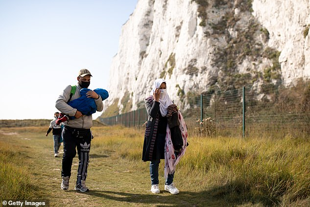 The legal team representing the three men, who arrived in Britain on small boats during the summer, had mounted a High Court challenge in a bid to halt the flight, which had been chartered by Home Office officials. Pictured: a migrant father was photographed walking with his wife and two children along the coastal path at Kingsdown Beach in Deal yesterday