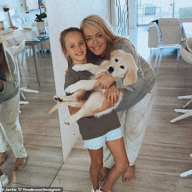 Costly creature comforts: Jackie added that she had no idea that under floor heating was an expensive luxury. She called it a 'waste of money' because she is rarely is barefoot in her home. Pictured is Jackie with her daughter Kitty in their apartment with a puppy
