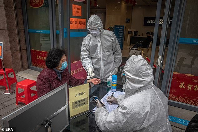 A worker in a protective outfit checks the body temperature of an elderly woman at the entrance of a bank, in Wuhan, China in March