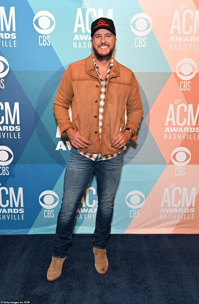 Relaxed: Luke Bryan, 44, stayed casual in a beige bomber jacket over a plaid shirt and blue jeans with beige suede boots