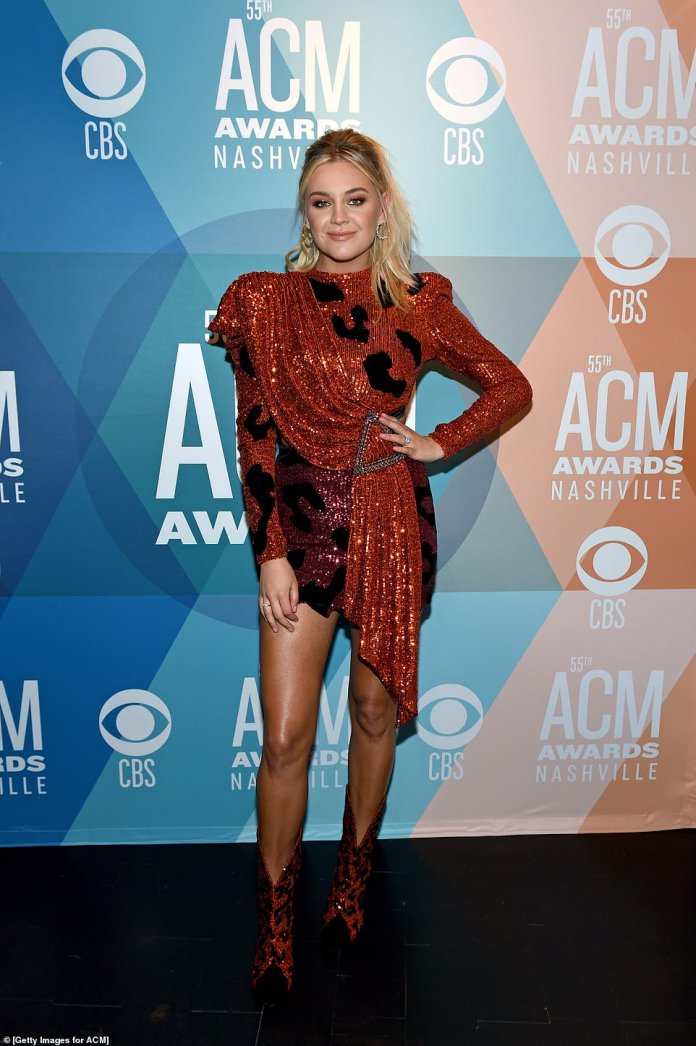 Stunning: Kelsea, 27, went for a leggy look in a two-tone sparkly mini dress with an asymmetric hem and matching cowboy boots