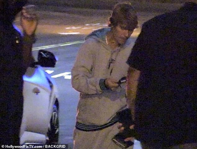 Masked-up: He scrambled to put on his black face mask, as they arrived at the upscale establishment for date night