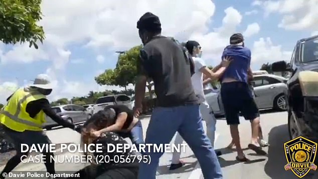 The woman continues to beat Joann as a man stops the attacker's mother from stomping on her