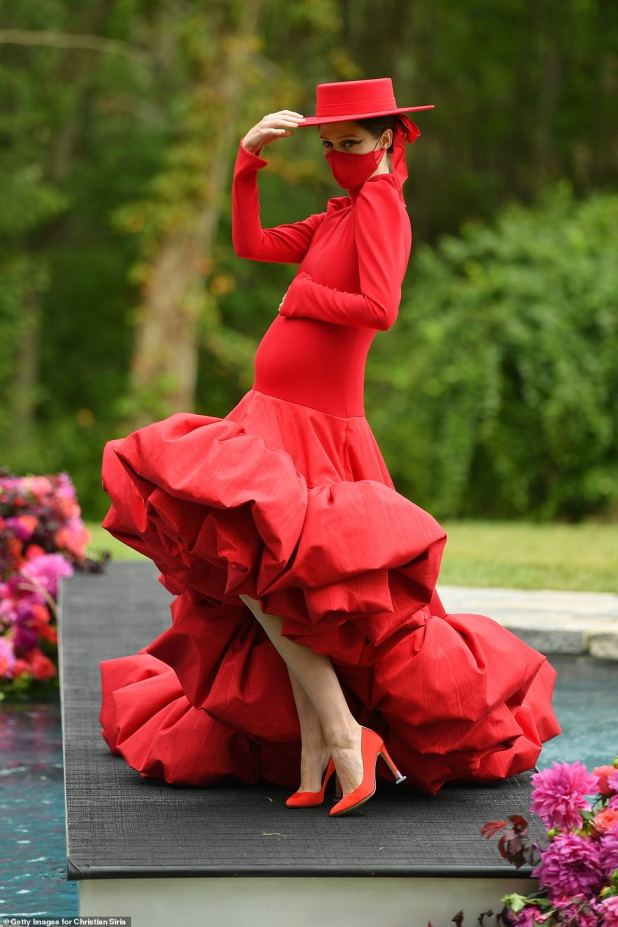 Poise: Before getting wet, Rocha, who was pregnant with her third child, looked stunning in a long-sleeved gown with a dramatic high-low ruffled hemline.