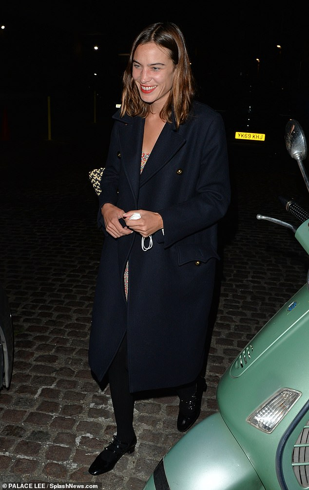 Stepping out in style: The British beauty cut a chic figure in a smart black coat over a floral dress as she enjoyed her night on the town with her boyfriend