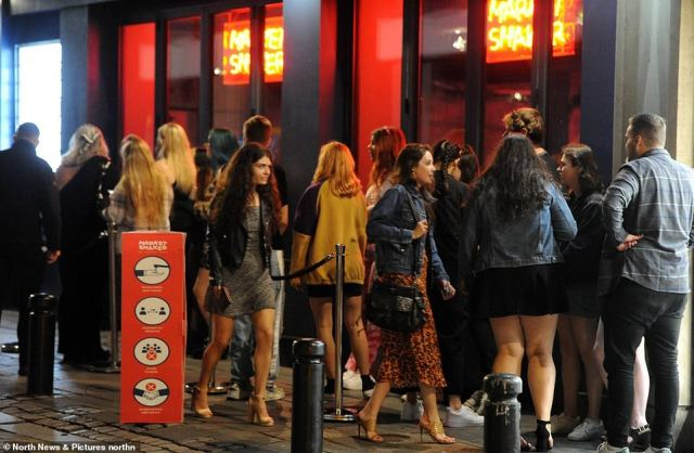 Pictured: Revellers in Newcastle wait in a line outside a bar in the city centre ahead of the new restrictions which come into force tonight