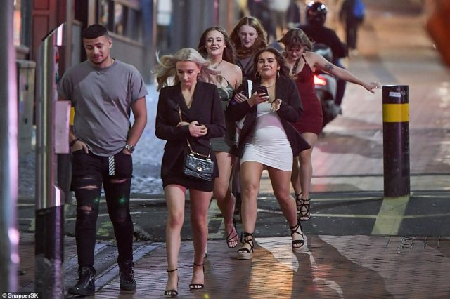 A group of students walk towards Be at One bar in Birmingham city centre during the city's local lockdown due to a spike in coronavirus